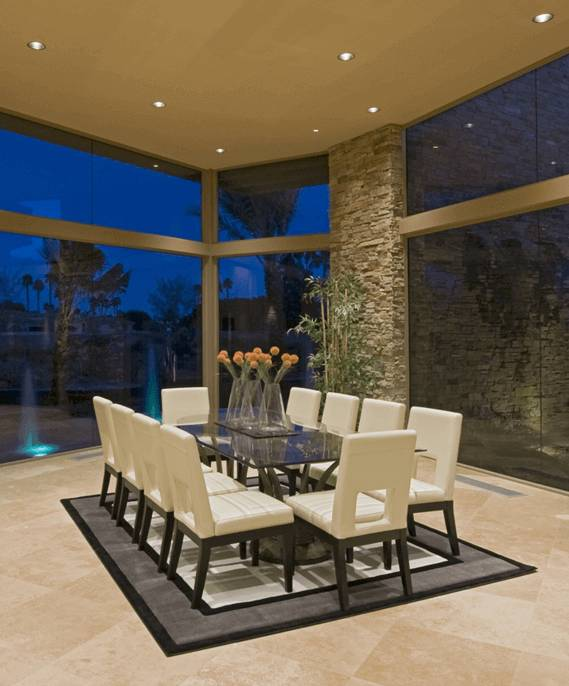 Elegant dining room with patio window and natural stone walls and flooring